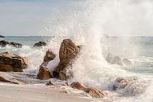 waves crashing into rocks on a shore