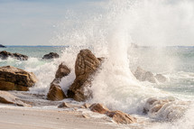 waves crashing into rocks on a shore