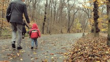 family walking on a fall path with a stroller