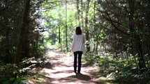 a woman walking alone on a path through the woods