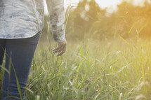 torso of a girl walking outdoors in a field of tall grass.