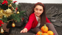 A girl child on the couch using a tablet at Christmas