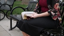 a woman sitting on a bench reading a Bible