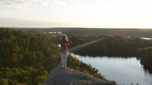 woman standing on the edge of a cliff taking in the view
