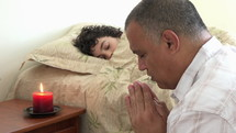 father praying next to his sleeping son