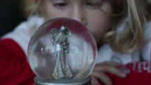 girl child staring at an angel snow globe