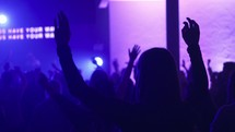 raised hands in an audience and purple stage lights