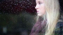 face of a young girl behind wet glass