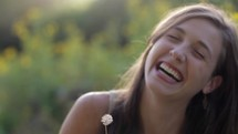 Joyful woman making a wish and blowing on a dandelion seed head.