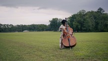 woman playing a cello outdoors
