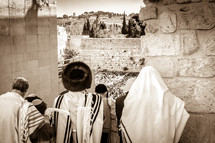 Orthodox Jews looking down at People praying at the Wailing Wall during a holiday.
