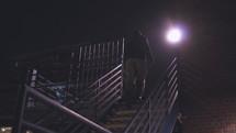a man walking up steps at night