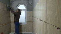 a man tiling a room