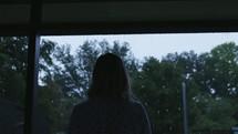 a woman watching the rain fall
