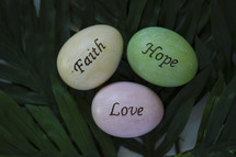 faith, hope, and love Easter eggs on palm leaves