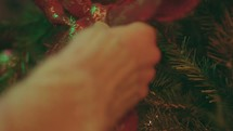 Christmas Tree Shoot - Woman hangs ribbon on a tree.