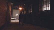 a man walking down a dark alley at night