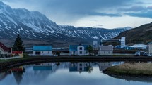 homes along a waterway with snowy mountains in the background