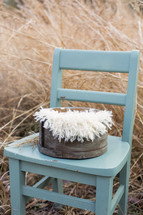 basket in a blue chair in hay
