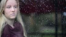 face of a teen girl behind wet glass