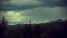 Timelapse of storm clouds moving over a tree-covered mountain range.