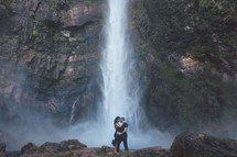 a couple holding each other in front of a waterfall