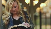 a woman reading a Bible near a gazebo