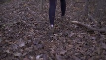 a woman in boots walking through a forest