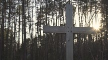 a wooden cross in front of a forest