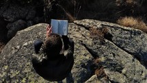 man reading a Bible on a mountaintop