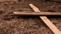 Wooden Cross with nails slowly falling on the ground