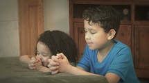 A brother and sister kneel to pray.