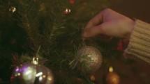 Christmas Tree Shoot - Woman hangs Christmas bulb on tree