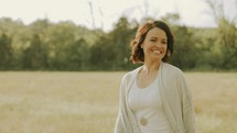 happy woman walking through a field