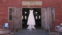 wedding dress hanging in on a barn