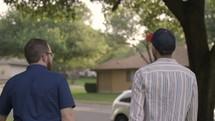 men walking down a neighborhood sidewalk talking