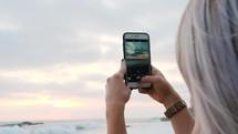 woman filming the ocean waves