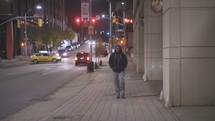 a man walking down a city sidewalk alone at night