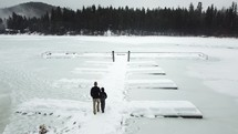 people walking on a dock over a frozen lake