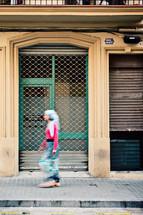 a woman walking on a sidewalk in Barcelona