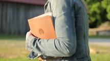 a woman walking caring a Bible on a farm