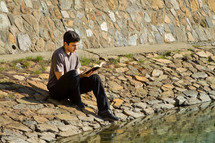 Man reading the Bible by a lake.