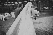 A bride and groom walking toward a dance floor