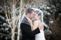 bride and groom kissing in the snow
