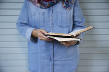 an elderly woman standing reading a Bible