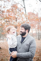 father holding his son outdoors in fall