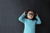 toddler girl wearing reading glasses against a chalkboard background.