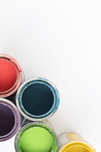 Open cans of colorful paint on a white background.