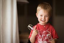 a little boy licking batter off a mixer