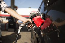 a woman filling up her car with gas at a gas station.